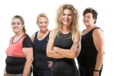Fitness instructor with a team of overweight middle aged women posing for group pic