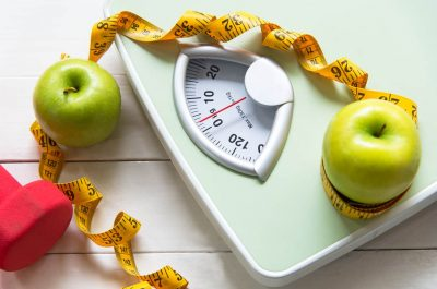 Green apple with weight scale and measuring tape for the healthy diet slimming . Diet and Healthy Concept