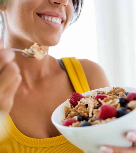 Portrait of beautiful young woman eating cereals and fruits at home.