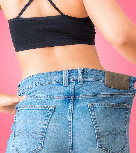 Close up portrait of young woman showing successful weight loss with her jeans on isolate background., Healthcare, Diet concept