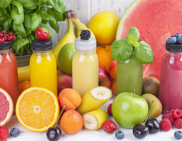 Many different fruits and berries and juices in plastic bottles. Watermelon, banana, applesin, blueberries, strawberries, basil. Vitamin and healthy food. Copy space.