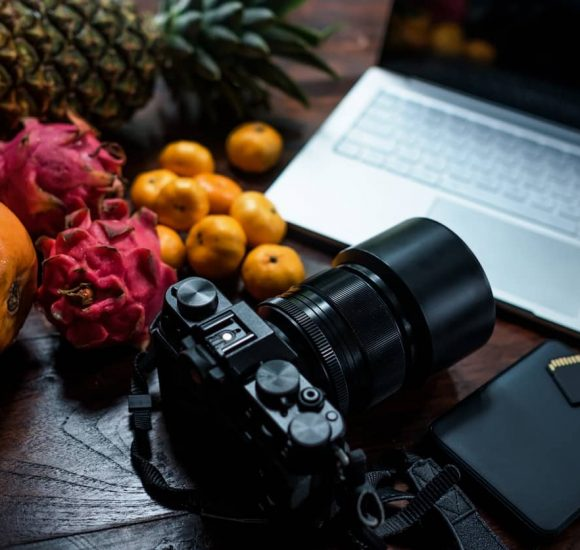 Tropical fruit near modern laptop and photocamera on wooden background. Tools for photo blogger anr travel journalist. Up view